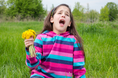 allergic: Sneezing girl sitting on green meadow and holding bouquet of dandelions Stock Photo