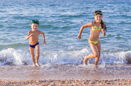Happy little kids runs from the sea photo