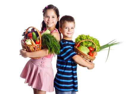 Smiling kids standing with vegetables in basket, isolated on white