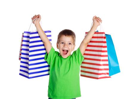 ni�os de compras: Ni�o feliz con bolsas de la compra, aislados en blanco