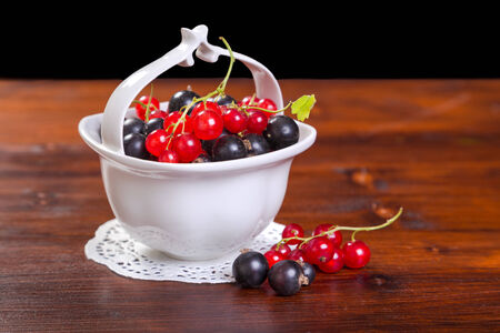 black and red currants in white bowl on wood table photo