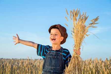 Happy boy with sheaf of wheat on the field photo