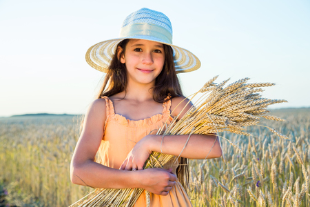 Smiling girl with sheaf of wheat standing on the field photo