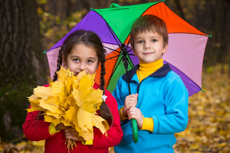 Two kids walking together in autumn park photo