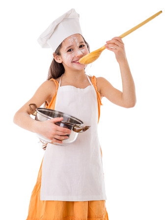 helpers: Smiling girl as cook tasting from the ladle with pot in hand, isolated on white