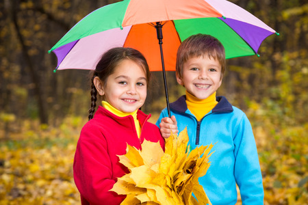 Two kids walking together on autumn park photo