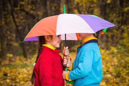 Two kids together under umbrella in autumn park photo