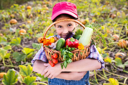Happy girl on pumpkin\'s field with basket of vegetables