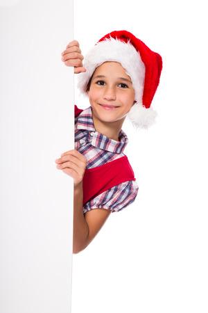 Happy girl in Santa hat peeking from blank whiteboard, Christmas advertisement photo