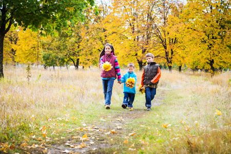 Three kids walking together in autumn park photo