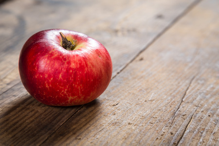 One red apple on old wooden board photo