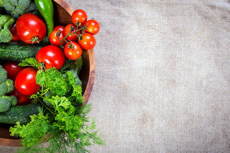 Plenty of colorful vegetables in wooden plate on linen background