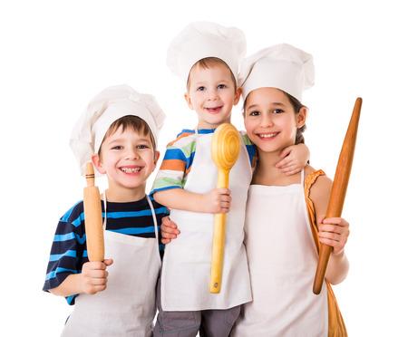 Drie kleine glimlachende chef-koks met een pollepel en deegrol, geïsoleerd op wit