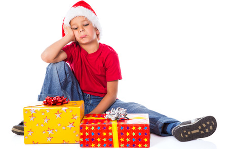 Sad boy with gift box in christmas hat, isolated on white photo