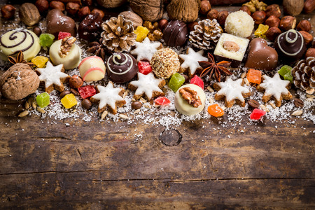 chocolate shavings: Wood background with sweets, candies, nuts, cookies and dried fruits