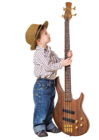 bass player: Little boy in hat standing with rock guitar, isolated on white