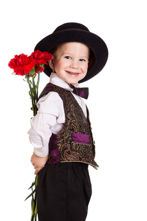 giving back: Smiling boy in hat hiding behind a bouquet of carnations, isolated on white Stock Photo
