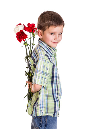 gift behind back: Little boy hiding the bouquet of carnations, isolated on white