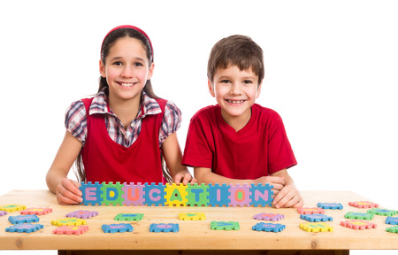 merge together: Two smiling kids at the table with puzzle letters, isolated on white Stock Photo