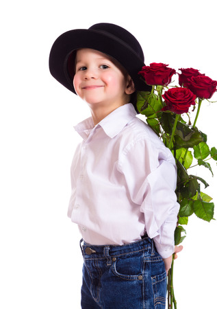 gift behind back: Little boy in black hat hide the bouquet of red roses, isolated on white