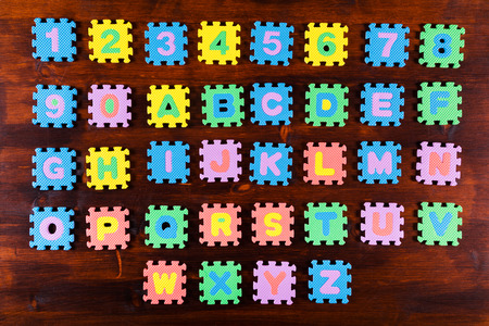 unattached: Colorful foam puzzle letters on wooden background, education concept