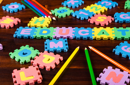 unattached: Colorful foam puzzle letters with pencils on wooden background, education concept