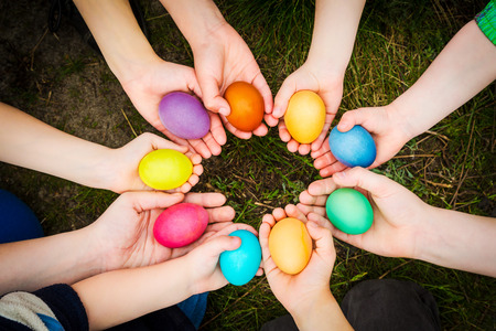 egg shape: Colorful easter eggs in child hands after egg-hunt