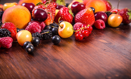 Assorted fresh berries on dark wooden table with copy space photo