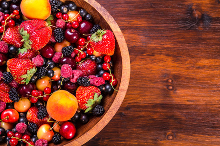 Assorted fresh berries in wooden bowl on wood background, copy space photo