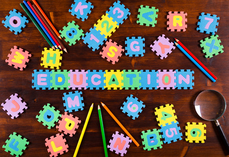 unattached: Colorful foam puzzle letters with pencils and lens on wooden background, education concept