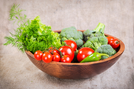 heathy diet: Plenty of colorful vegetables in wooden plate on linen background