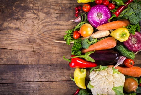 cutting vegetables: Plenty of colorful vegetables on wooden table with copy space Stock Photo