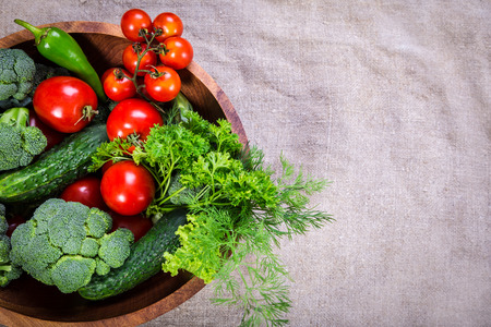 heathy diet: Plenty of colorful vegetables in wooden plate on linen background with copy space Stock Photo