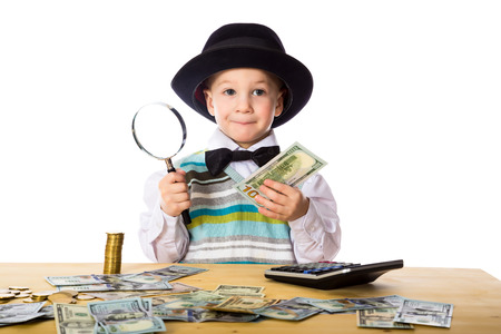 Little boy in black hat counting money on the table, isolated on white