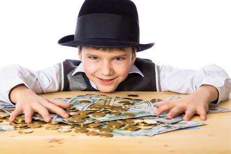 Happy boy in black hat with money on the table, isolated on white Imagens - 37152957
