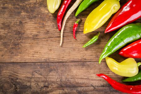 cutting vegetables: Plenty of colorful peppers on wooden background with copy space
