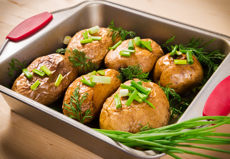 oven tray: close up of baked potatoes with green onion in oven tray Stock Photo