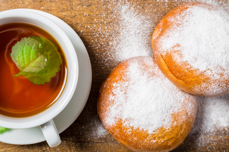 powdered sugar: Tea cup with sugar powdered buns on wooden background