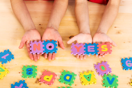 yes or no: Colorful foam puzzle letters words yes and no in kids hands on wooden background