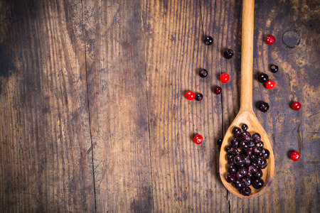 black currant in spoon and viburnum on wooden background with empty copy space photo