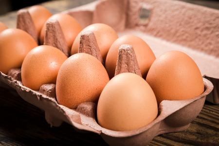 reciclable: Huevos del pollo en bandeja de cart�n reciclable en mesa de madera