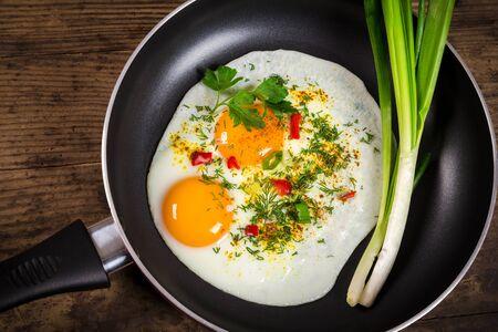 huevos fritos: dos huevos fríen con verdes en la cacerola en mesa de madera