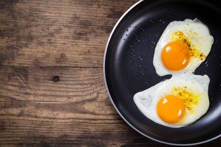 two frying eggs in pan on wooden table with copy space photo