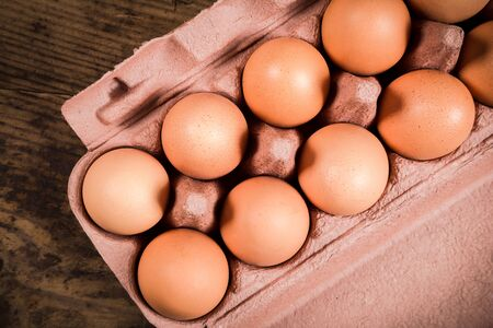 recyclable: Chicken eggs in recyclable carton tray on wooden table, top view Stock Photo