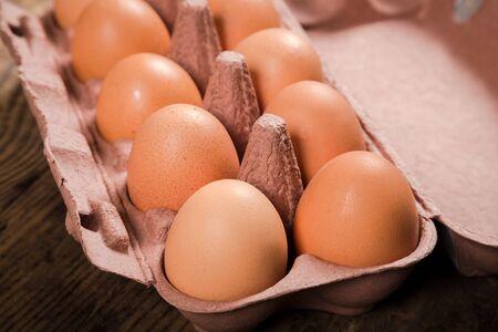 reciclable: Huevos del pollo en bandeja de cartón reciclable en mesa de madera