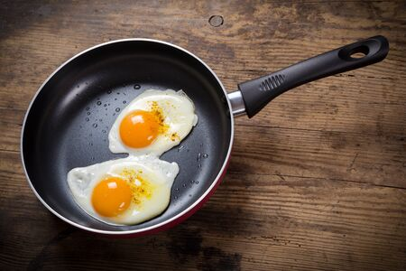 two frying eggs with spices in pan on wooden table photo