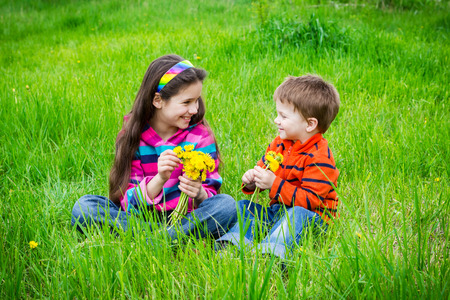 Two kids with bouquet of dandelions on green grass, meadow photo