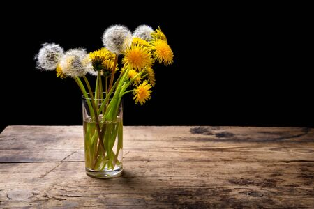 Still life with bunch of dandelions in glass on brown wood table with empty space for text photo