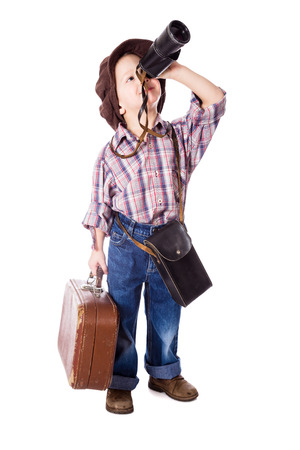far away look: Traveling little boy with old suitcase looking to spyglass, isolated on white Stock Photo