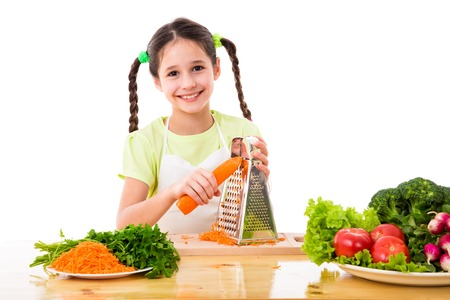 zanahoria: Muchacha sonriente rallar las zanahorias en la mesa con verduras, aislados en blanco Foto de archivo